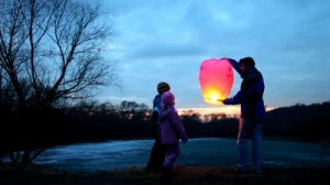 stock-footage-father-son-and-daughter-start-glowing-pink-chinese-lantern-of-winter-forest-then-look-upwards-at